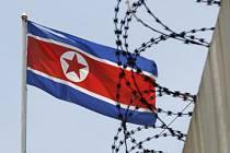 Severokorejská vlajka za ostnatým drátem. Ilustrační foto.