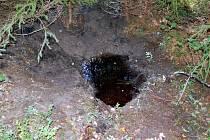 Jáma v lese u Krásna, kde vrah zakopal rozřezaného muže z Německa.