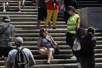 Policistka v Římě vysvětluje turistce, že sezení na Španělských schodech je zakázané.