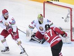 Ryan O'Reilly z Kanady (vpravo) překonává brankáře Běloruska Dmitrije Milchakova.