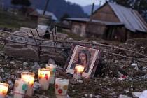 Lidé kladou na místo, kdes stával dům a sklad, svíčky a obrázky
