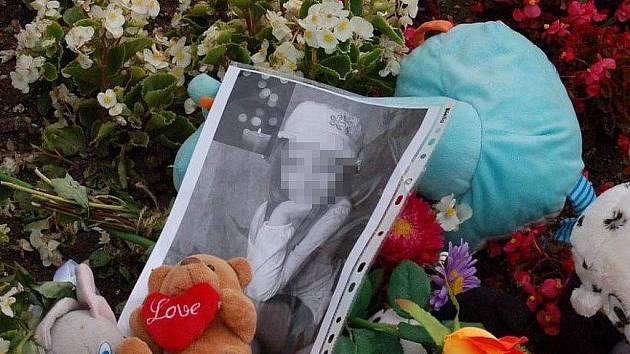 Na pietním místě před základní školou je uprostřed svíček a hraček i fotografie zavražděné dívky.