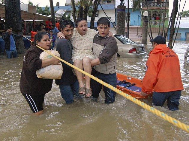 Sousedé pomájaí do bezpečí ženě v ničivými záplavami postiženém státe Tabasco.