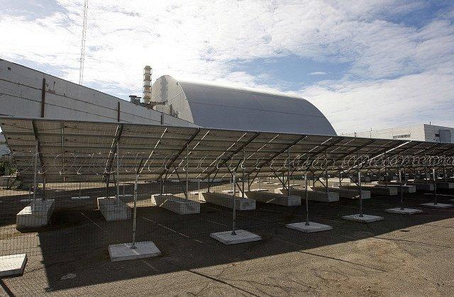 Solární elektrárna v Černobylu na Ukrajině. V pozadí sarkofák jaderné elektrárny.