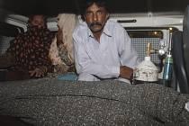 Mohammad Iqbal v sanitce s tělem ukamenované manželky.