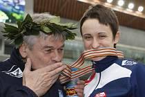 Petr Novák, kouč Martiny Sáblíkové, líbá zlatou medaili, kterou jeho svěřenkyně vybojovala na trati 5000 metrů.