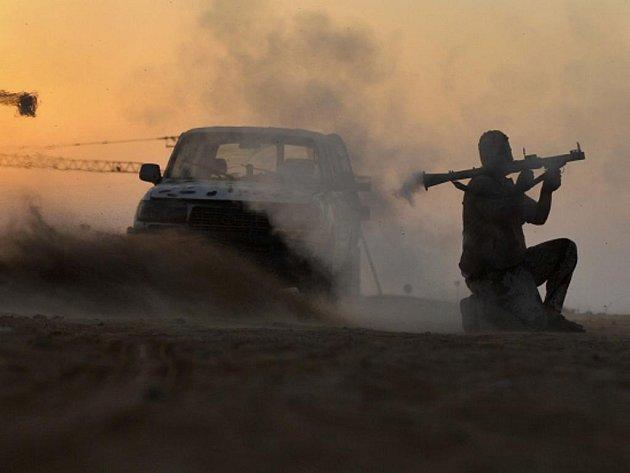 Libyjský povtalec střílí raketometem v severolibyjském přístavu Syrta.