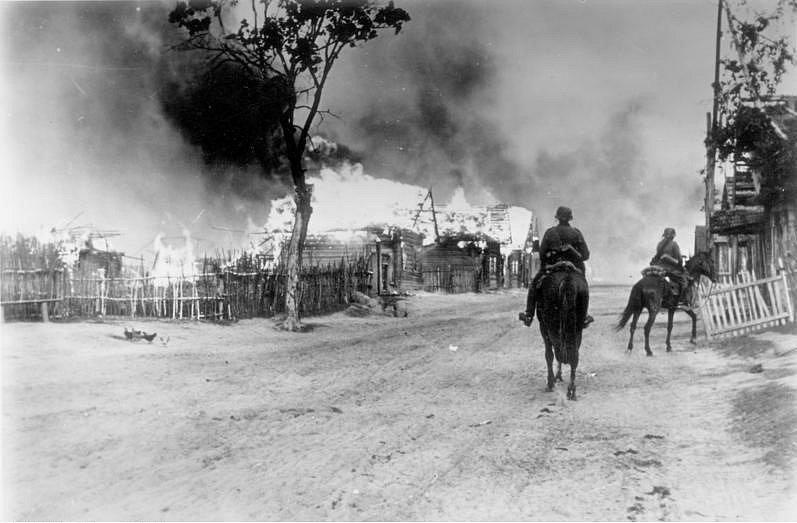 Německé jezdectvo projíždí hořící běloruskou vesnicí u Mogileva