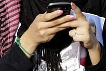 Dívka s mobilním telefonem v ruce - ilustrační foto
