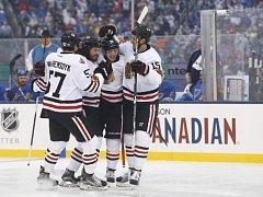 Michal Kempný (druhý zleva) se raduje se spoluhráči z Chicaga z gólu v duelu NHL pod širým nebem.