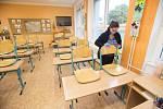 Žena dezinfikuje židli 15. října 2020 na základní škole npr. Eliáše v Pardubicích