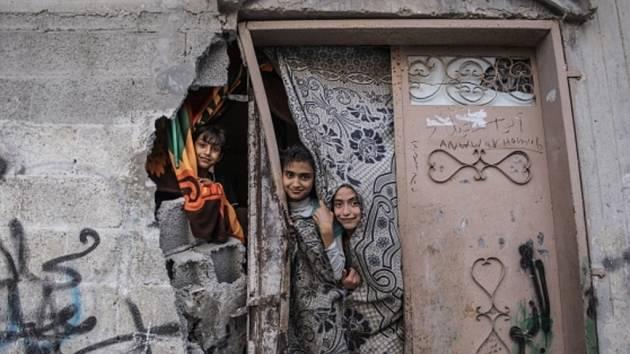 Palestinské děti vyhlížejí ze svého zničeného domu ve městě Beit Hanoun v severní části Pásma Gazy.
