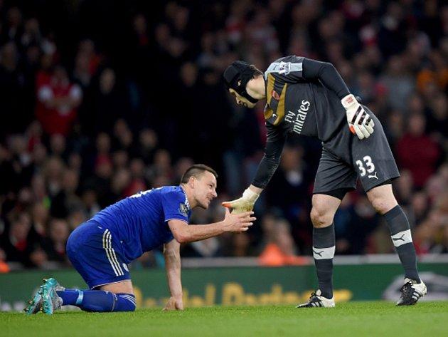 Brankář Arsenalu Petr Čech (vpravo) pomáhá na nohy svému bývalému spoluhráči Johnu Terrymu z Chelsea.