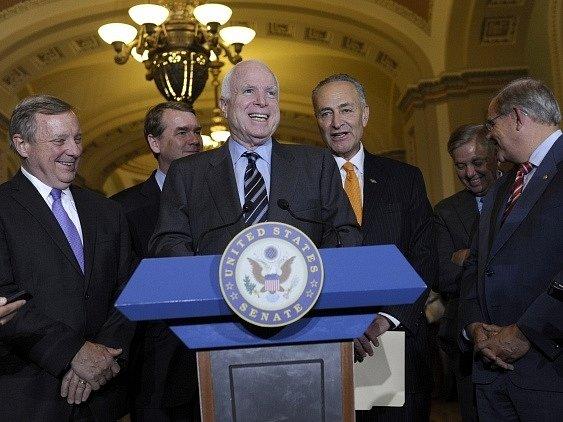 Senátor John McCain (uprostřed) s kolegy u řečnického pultu poté, co byl schválen imigrační zákon.