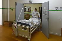 Zdravotník v sokolovské nemocnici převáží pacienta na lůžkové oddělení určené pro nemocné s covidem-19