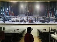 Číňan si v muzeu prohlíží obraz, zachycující kapitulaci japonských okupantů v čínském Nankingu v roce 1945. Válka i po více než 60 letech stále zatěžuje vztahy mezi Pekingem a Tokiem.