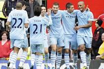 Edin Džeko (uprostřed) slaví se spoluhráči z Manchesteru City gól proti Manchesteru United.