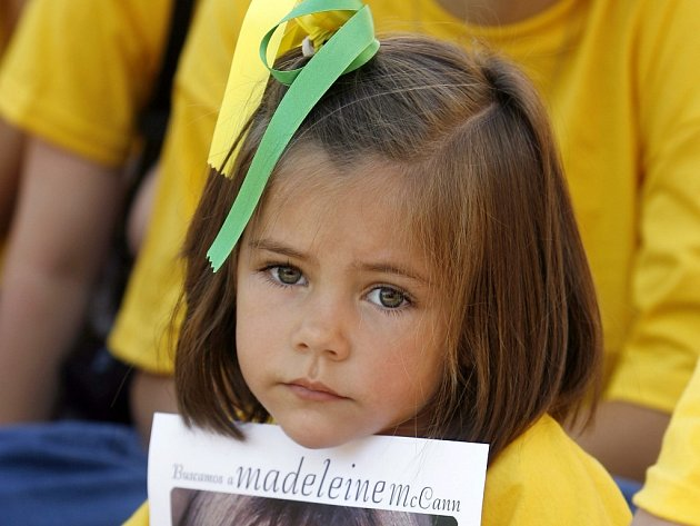 Dívenka v centru Madridu drží v rukou fotografii čtyřleté Maddie McCannové. Maddie někdo unesl 3. května z pokoje v portugalském Algarve, kde byla s rodiči na dovolené.