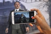 Inkriminovaná vosková figurína Adolfa Hitlera na pozadí koncentračního tábora