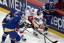 Čeští hokejisté Jan Kovář (třetí zleva) a Tomáš Hertl se snaží prosadit proti Švédsku.