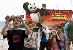 """Turisté fotografují u reklamního panelu pro animovaný film """"Kung Fu Panda"""""""