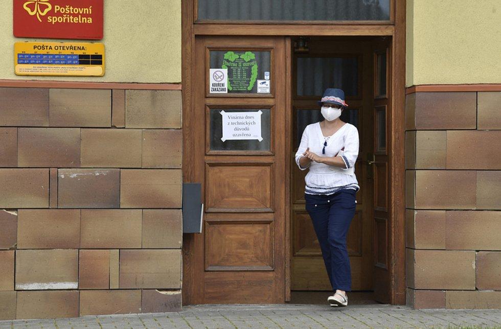 Žena s rouškou u pošty ve Vlčnově