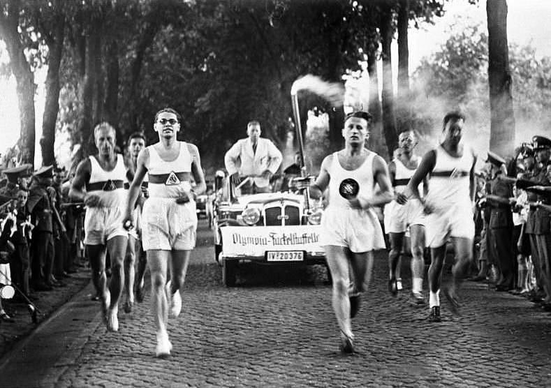 Běžci přináší pochodeň s olympijským ohněm na olympiádu v Berlíně v roce 1936. Tradice běžecké štafety byla založena právě na těchto hrách.