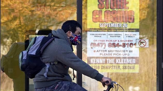 Muž s rouškou projíždí na kole kolem zavřeného obchodu ve městě Wilmette v americkém státě Illinois