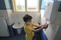 Žák v roušce 1. třídy ZŠ Komenského ve Světlé nad Sázavou si utírá ruce na toaletě do papírové utěrky (na snímku z 25. května 2020)