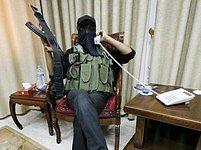 """Člen ozbrojeného křídla Hamásu sedí v pokoji prezidentského sídla v Gaze, kde Mahmúd Abbás dřív přijímal hosty. """"Haló, Condoleezza Riceová?"""" předstírá."""