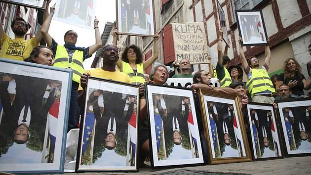 Demonstranti na summitu G7 ve Francii drží portréty francouzského prezidenta Emmanuela Macrona