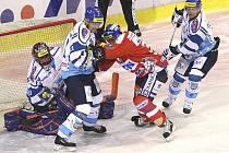 Útočník Pardubic Adam Pineault (v červeném) se snaží prosadit mezi Milanem Tomanem (druhý zleva) a Radkem Bělohlavem.