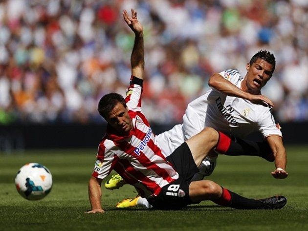 Cristiano Ronaldo z Realu srdnatě bojuje o míč s Carlosem Gurpegim z Bilbaa.