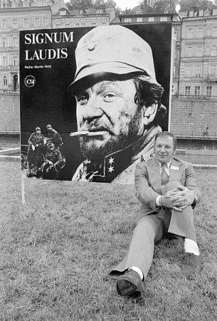 VLADO MÜLLER. Na karlovarském festivalu vr. 1979před plakátem kfilmu Signum laudis.