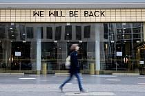 Žena prochází kolem zavřeného kina v Berlíně 20. března 2020