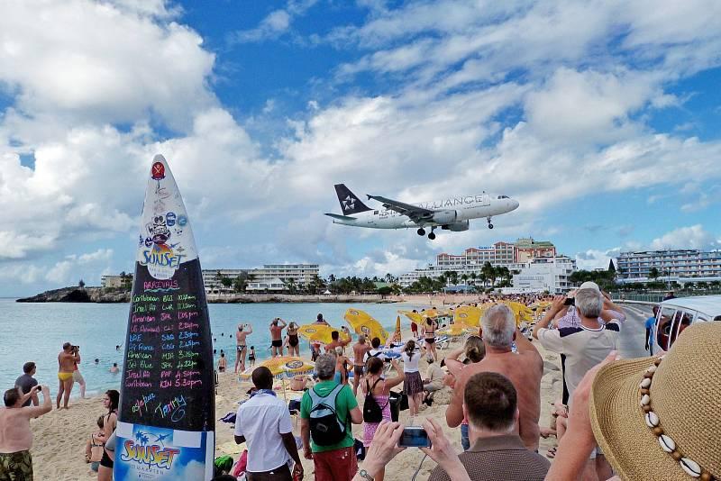 Těsně nad hlavami lidí na pláži prolétávají letadla na ostrově Svatý Martin v souostroví Malé Antily. Letiště princezny Juliany se totiž nachází hned vedle pláže.