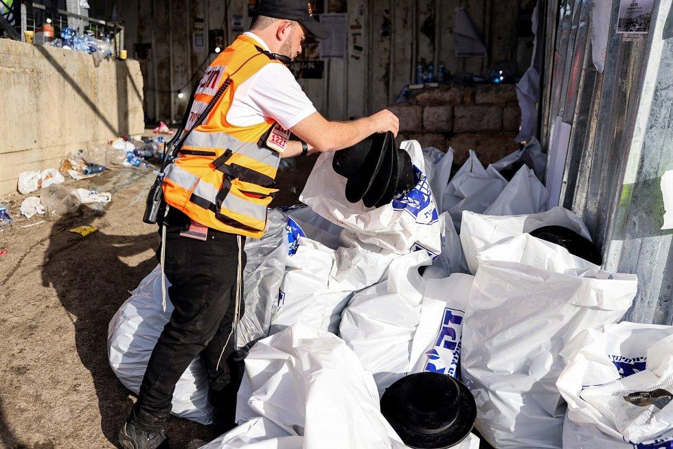 Pracovník sbírá klobouky ortodoxních Židů na hoře Meron v severním Izraeli.