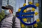 Muž v roušce prochází kolem znaku eura před sídlem Evropské centrální banky ve Frankfurtu nad Mohanem, 5. května 2020.