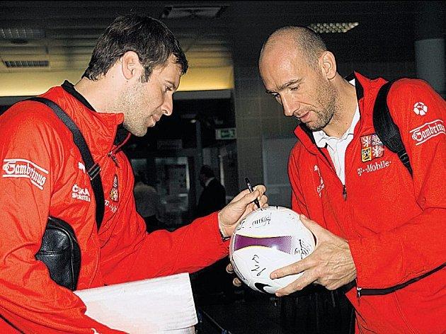 Brankář fotbalové reprezentace Petr Čech podepisuje před odletem na soustředění do Seefeldu v letištní hale na Ruzyni míč Janu Kollerovi.