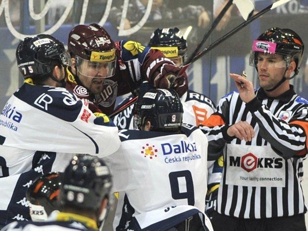 Hokejisté Vítkovic Richard Stehlík (vlevo), Jan Káňa (dole) a Petr Kumstát ze Sparty (uprostřed) si vyřizují účty.
