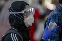 Žena v roušce, ochranných brýlích a rukavicích čeká 26. března 2020 u terminálu na letišti ve Frankfurtu nad Mohanem