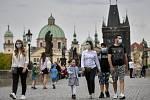 Lidé v rouškách proti šíření koronaviru 9. května 2020 na pražském Karlově mostě