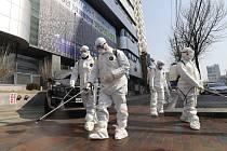 Pracovníci v ochranných oděvech dezinfikují prostor před kostelem v jihokorejském Tegu na ssnímku z 20. února 2020.