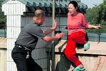 Čínský policista se snaží zachránit sebevražedkyni. V Číně jsou už stránky radící, jak spáchat sebevraždu, blokovány.