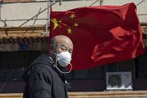 Muž s rouškou u nemocnice v Pekingu