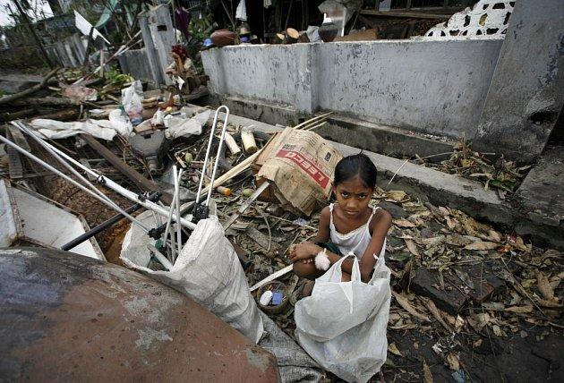 Dívka hledá v troskách svého domu poslední zbytky věcí.