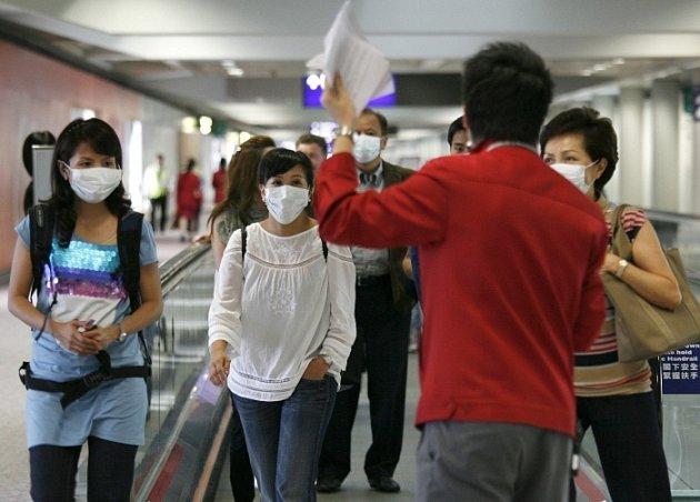 Cestující na letišti v Hongkongu se chrání rouškami před nákazou  novou smrtelnou nemocí zvanou prasečí chřipka.