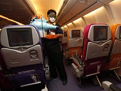 Člen posádky rozšiřuje desinfekční látku v letadle thajských aerolinií v Bangkoku.