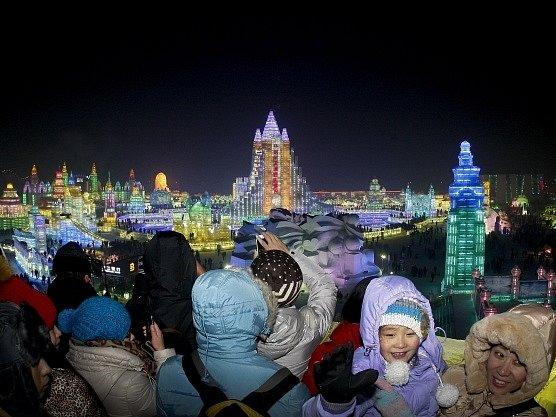 Lidé si fotografují barevné sochy z ledu při zahajovacím ceremoniálu.