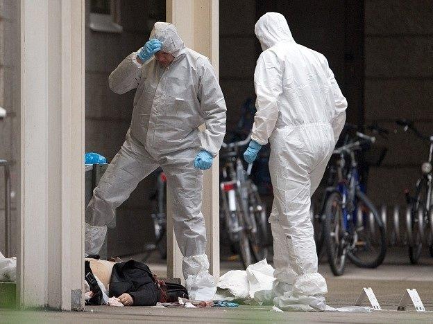 Vyšetřovatelé zkoumají tělo jedné z obětí.